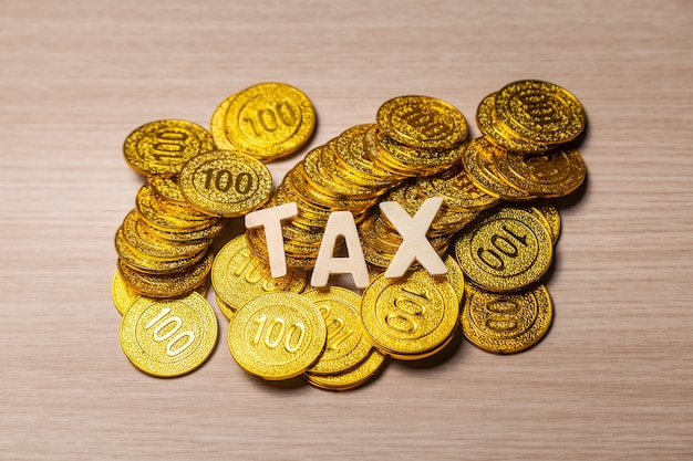 Tax woth on coins on wooden table