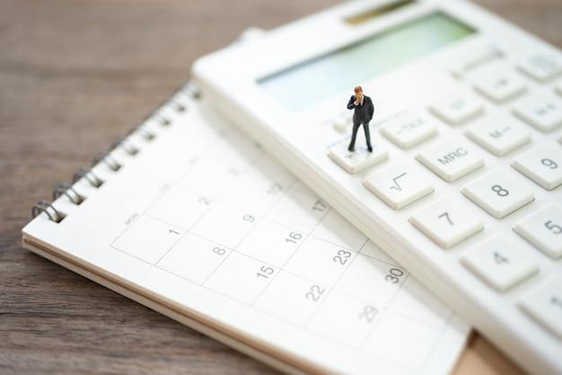 ミニチュアの人々電卓で年間のキューの年間収入(tax)を支払います。