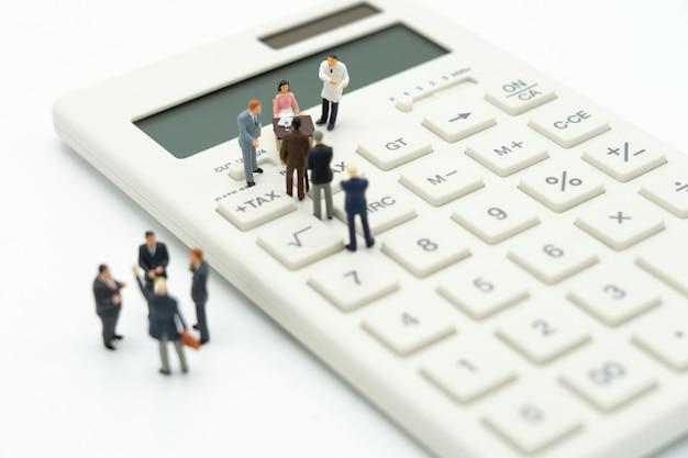ミニチュアの人々は電卓でその年のキューの年収(tax)を支払います。