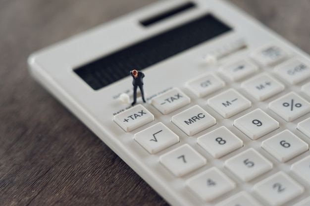 ミニチュアの人々電卓でその年のキューの年収(tax)を支払う