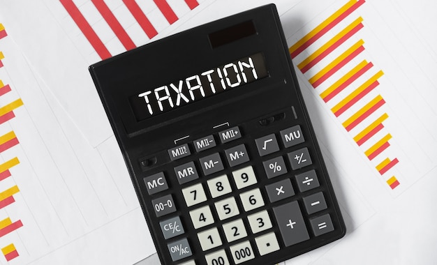 Taxation word on calculator accounting and bookkeeping concept