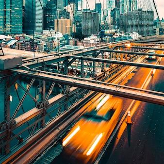 Taxi cab crossing the brooklyn bridge in new york, manhattan skyline in background