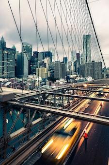 ニューヨークのブルックリン橋を渡るタクシー、マンハッタンのスカイラインを背景に
