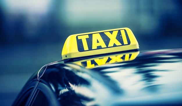 Автомобиль такси ожидает пассажиров в городе. такси свет на кабине автомобиля, готового к перевозке пассажиров