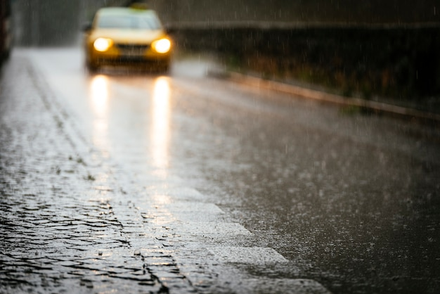 비가 오는 동안 젖은 아스팔트 위를 순환하는 택시. 비 개념입니다.