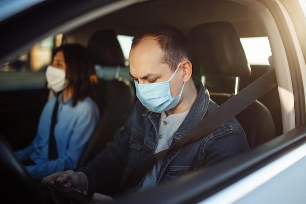 코로나 바이러스 전염병 동안 교통 체증을 기다리는 동안 택시 운전사가 모바일 휴대 전화로 채팅하고 멸균 의료 마스크를 착용하고 있습니다.