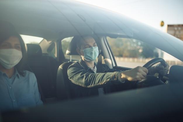 멸균 의료 마스크를 쓰고 택시 운전사는 운전대에 손을 잡습니다.