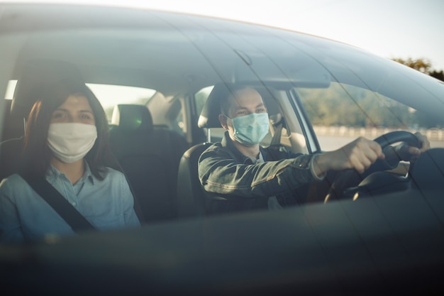 Taxi driver wearing sterile medical mask hold his hands on the steering wheel.