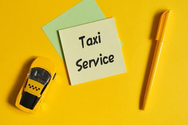 노란 벽에 장난감 자동차 옆 스티커에 비문으로 택시 서비스 개념