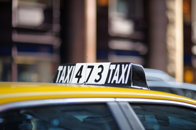 Taxi sign in big city close up