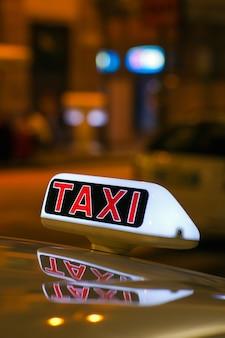 밤에 밀라노 거리에 주차 된 택시에서 택시 기호