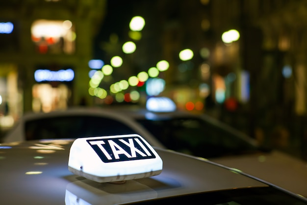 Taxi sign illuminated in the city at night