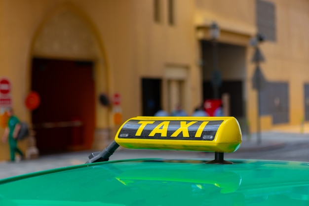 Taxi sign on the roof of a car in a street