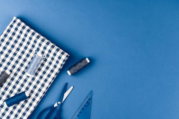 Аксессуары tayloring на классическом синем столе, вид сверху