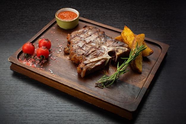 Стейк тбоне на деревянной доске с картофельным соусом сборщики вишни на темном столе