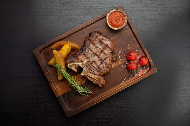 Tbone steak on a wooden board with potatoes sauce cherry pickers on a dark table