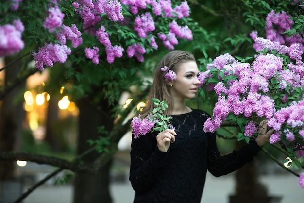 봄 꽃으로 둘러싸인 아름다운 젊은 여성의 tdoor 패션 사진