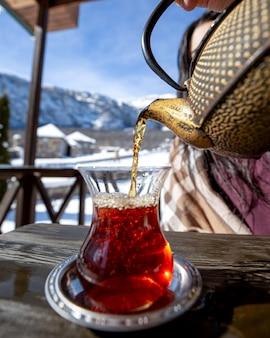 山を背景に黒茶を注ぐ女性