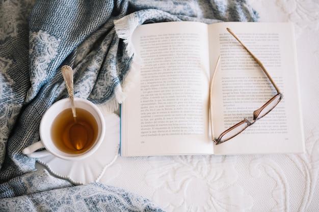 Чай и книга с очками на кровати