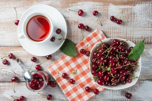 Чай и вишневое варенье на деревянном столе. сладкие спелые ягоды в миске. вкусный завтрак. у
