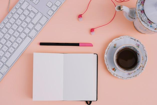 ノートとキーボードの近くの紅茶とイヤホン