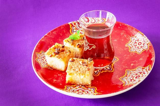 Чай и пирожные basbousa или namoora - традиционный арабский сладкий манный торт с орехами, кокосовой и апельсиновой водой. копировать пространство сиреневый космос.