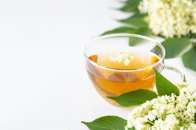 ニワトコからお茶とシロップの花白い背景の上のサンブカス。コピースペース