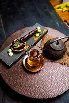 Tea in armudu glass, chinese teapot and chocolate tartaleta