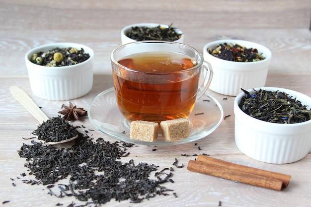 木製の素朴な背景にボウルにお茶のさまざまな種類のお茶の品揃えは、カップにお茶を用意しました