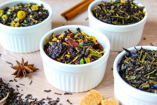 お茶の品揃え木製の背景に白いボウルにさまざまな種類のお茶