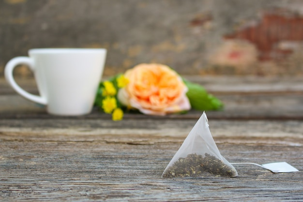 Tea bag on background of rose and and cup of tea.