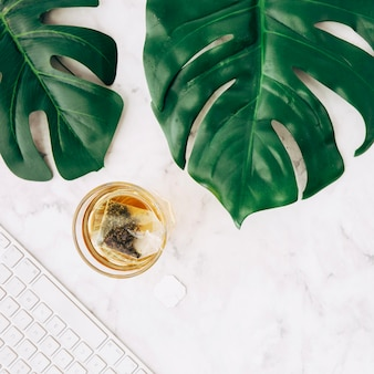 Tea bag in a glass transparent cup; green monstera leaves and keyboard on white marble textured backdrop