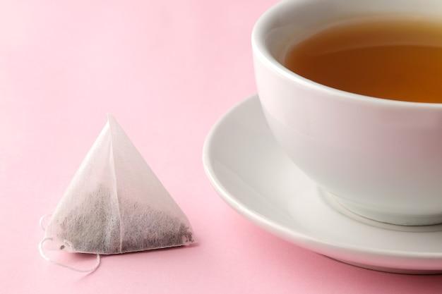 繊細なピンクの背景にティーバッグピラミッドとお茶のカップ。お茶を作る。