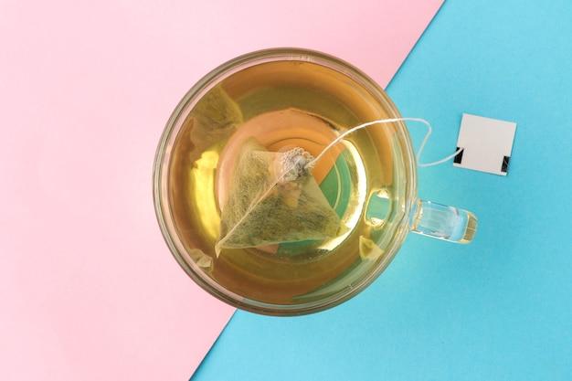 優しい青とピンクの背景にティーバッグピラミッドとお茶のカップ。お茶を作る。上面図