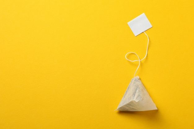 Tea bag with label on yellow, space for text