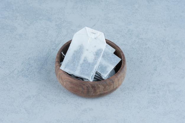 Bustine di tè in una ciotola su marmo.