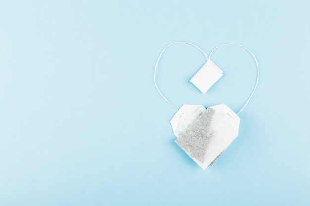 Tea bags in form of heart on blue background.