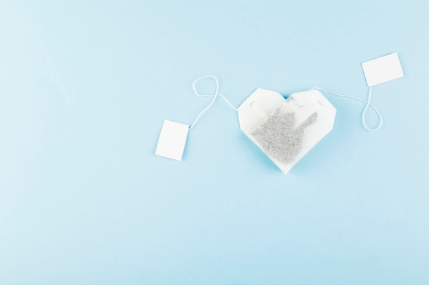 Tea bags in form of heart on blue. top view, copyspace