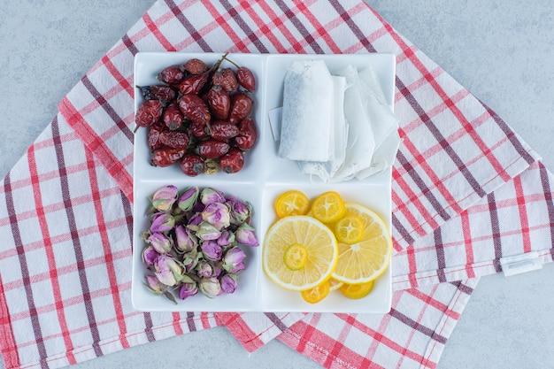 Чайные пакетики, нарезанный лимон, сухой шиповник и цветок в миске на мраморе.
