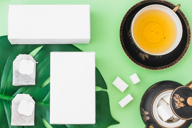 Tea bags, sugar cubes, and boxes with herbal tea cup on green background