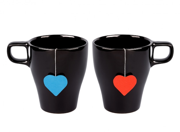 Tea bags with red and blue heart-shaped lables in cups isolated