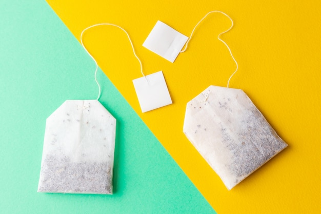 Tea bags with white labels on a pastel green and bright yellow background