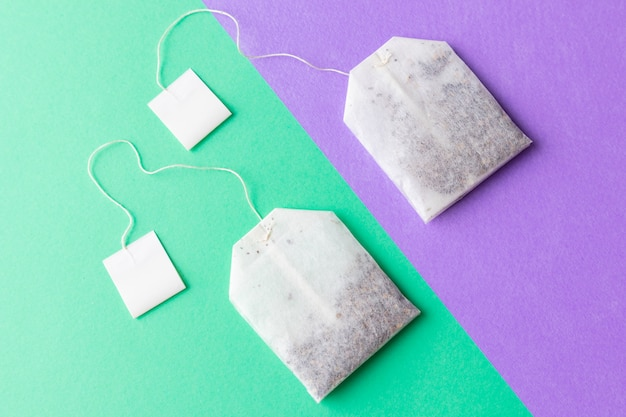 Tea bags with white labels on a pastel green and purple background