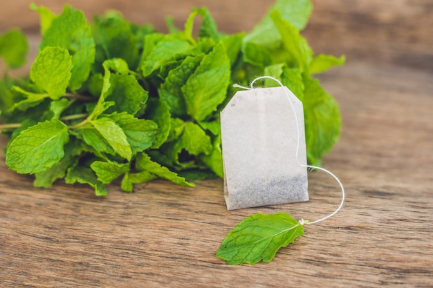 Tea bags on wooden table with fresh melissa, mint. tea with mint concept.