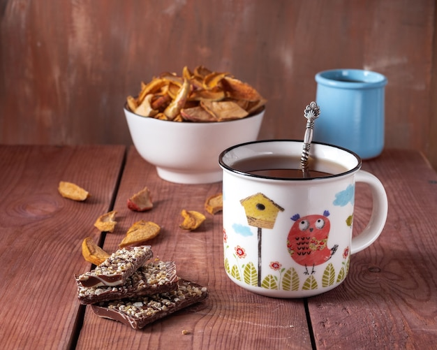 Tea in a ceramic mug and apple chips in a white flint and apple syrup in a blue clay jar