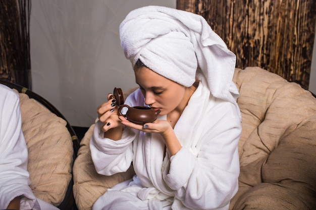 Tea ceremony after the sauna. girls in white coats drink chinese tea