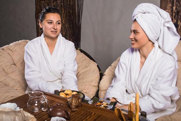Чайная церемония после сауны. девушки в белых халатах пьют китайский чай