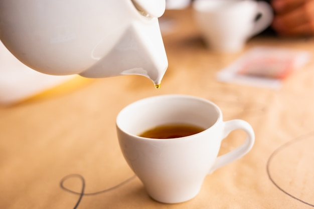 Tea ceremony soft focus pouring hot drink from white porcelain kettle to white cup autumn