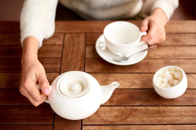 Чайная церемония со столом для чая с белым чайником, сахарницей и чашкой на деревянном столе. чайные традиции