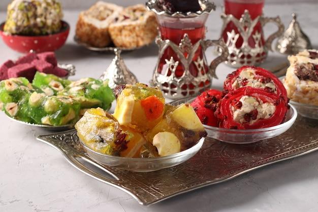 灰色の背景の金属トレイにトルコのお菓子と茶道。閉じる。水平フォーマット